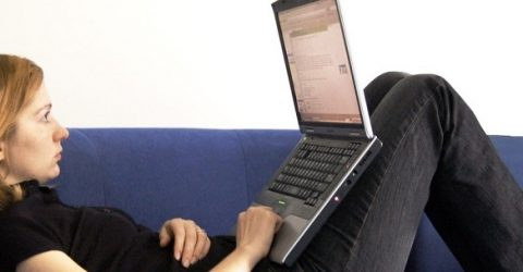 photo of woman sitting on blue sofa with laptop