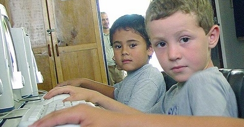 photo of three children sitting in front of computers