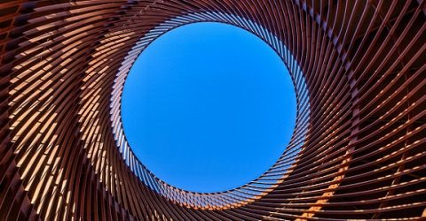 photo of a blue sky looking up through cylindrical structure