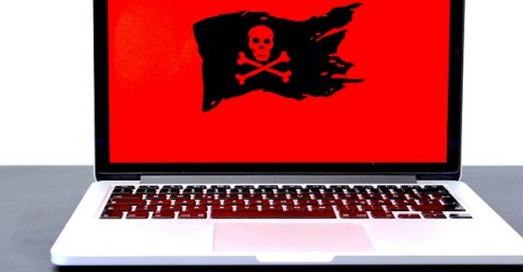 a laptop with a skull and cross bones flag displayed on screen