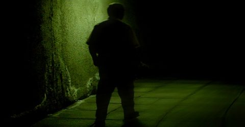 silhouette of a figure down a dark alley