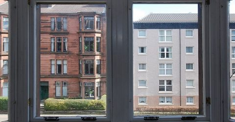 photo of two buildings from inside a window