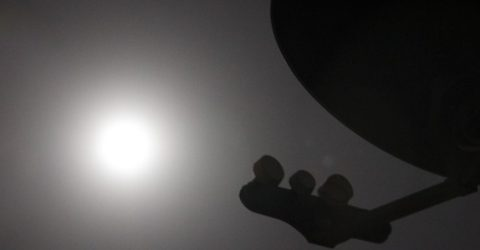 silhouette of satellite dish with sun behind it