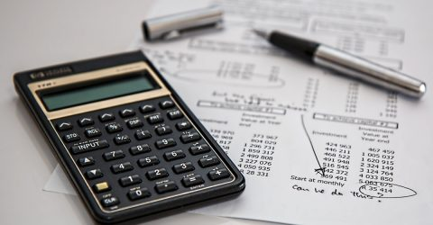 calculator and pen on a piece of paper with investment figures