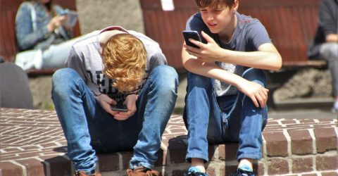 Two children playing on a smart phone