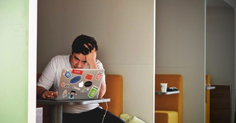 Man looking stressed while using a macbook