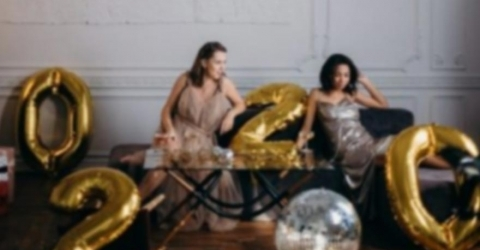 Women at New Years Eve party 2020 with disco balls and balloons on sofa