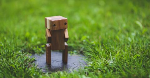 wooden model of a  robot walking on some grass