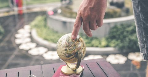 Someone pointing at a globe with a passport