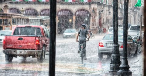 person riding a bike in a storm