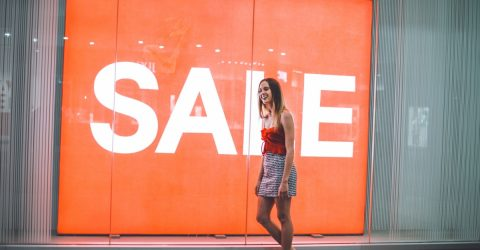 a woman smiling and walking on a street outside a shop with a sale sign inside