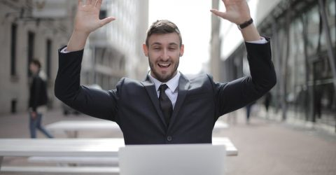 A man raising his hands in celebration while using a laptop
