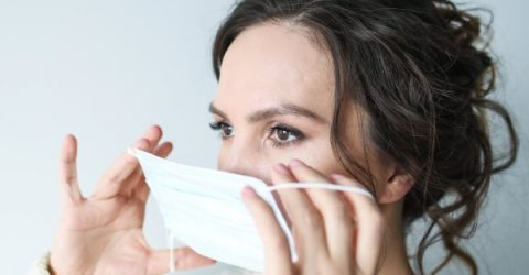 A woman putting on a surgical mask to avoid Coronavirus transmission