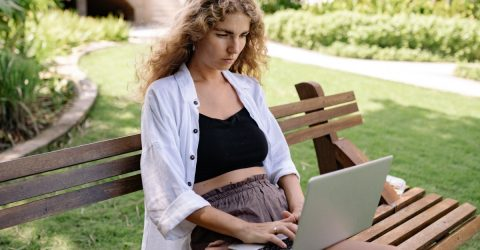 A blonde woman using a silver laptop outside on a bench