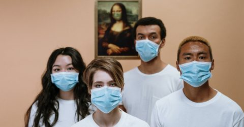 a group of young people wearing surgical masks because of the covid-19 pandemic