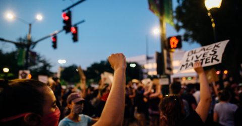 a group of protesters holding signs and raising their fists at a 2020 black lives matter protest