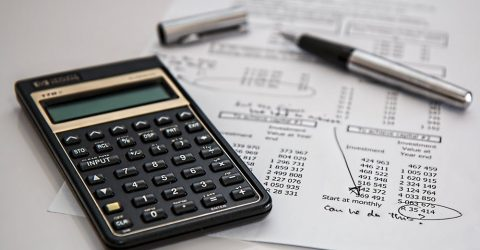 a calculator and some household bills on a table