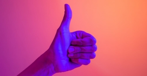 A person's hand doing a thumbs up in neon lighting