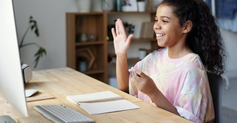 a girl waving to someone on a video call using a computer