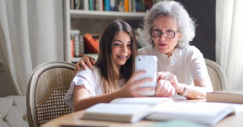 a grandmother and granddaughter using a smart phone together