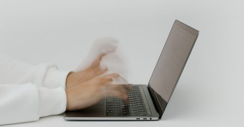 someone using a laptop and typing very fast