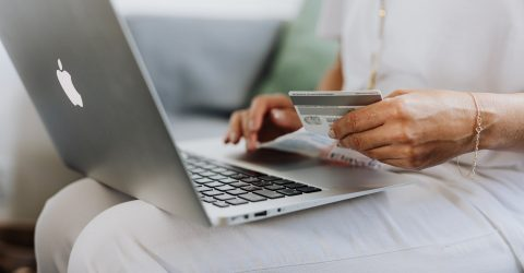 a person holding a credit card and using a macbook