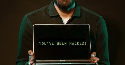 a man holidng a laptop that says 'you've been hacked' on the screen