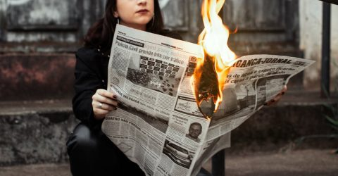 a woman holding a burning newspaper